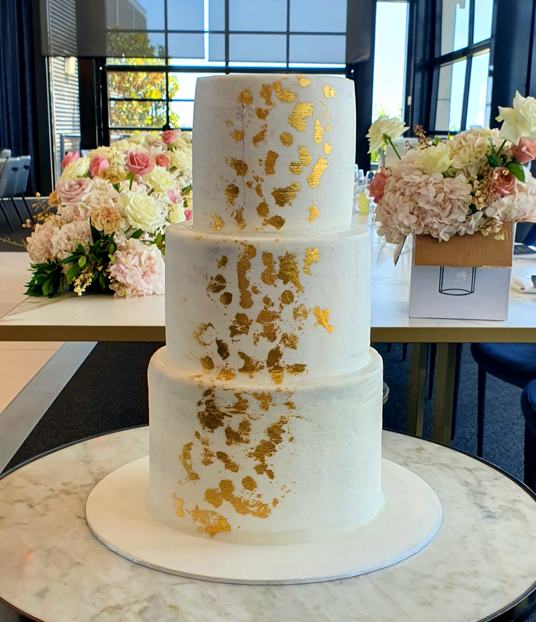 3 tier smooth buttercream cake with gold leaf accents from $550